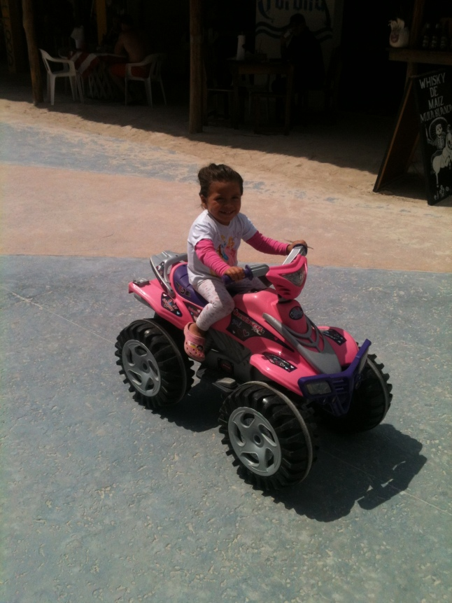 Little girl riding her toy ATV on malecon.