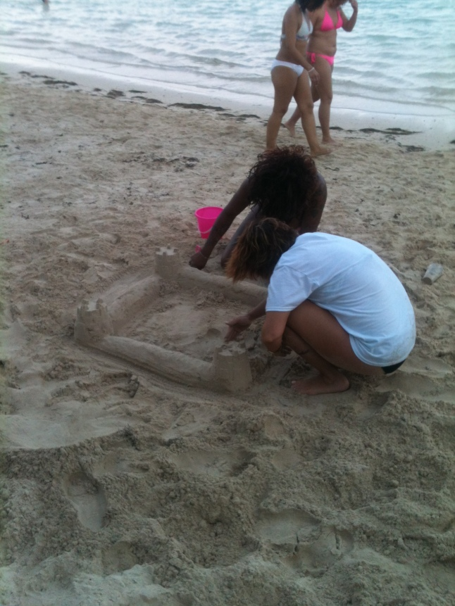 Cruise ship tourists making sand castle on beach.