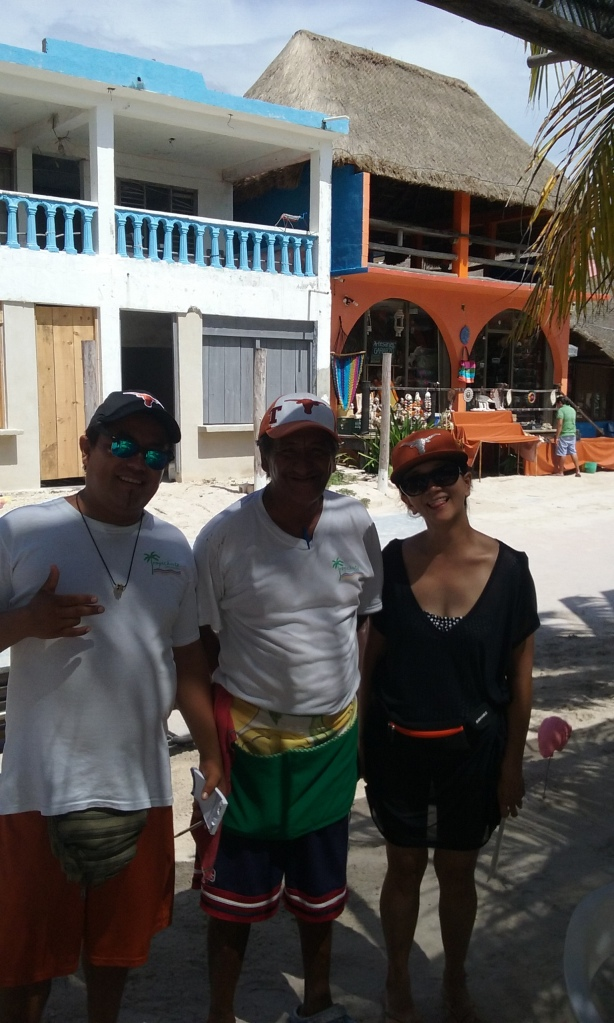 Kane and Blondie waiters from the Tropicante in their Texas hats, with a woman from the cruise ship in her Texas hat.